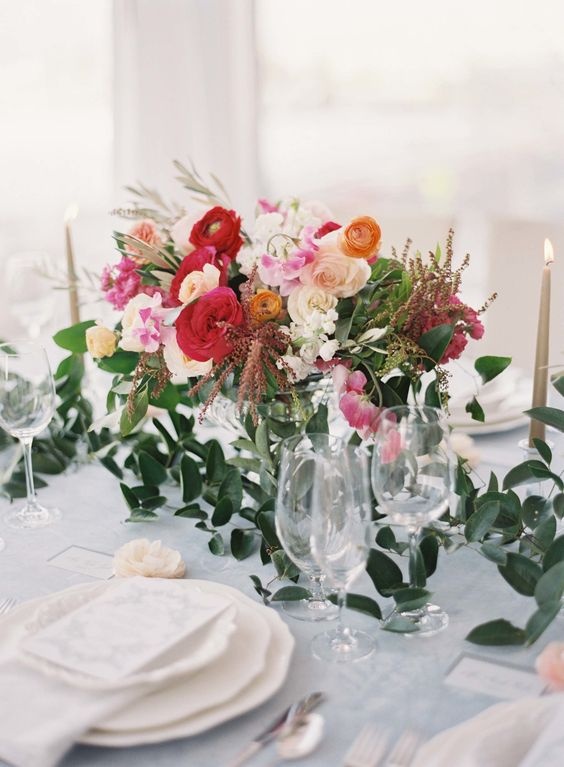 a bright spring wedding centerpiece in white, pink, hot red and orange plus greenery