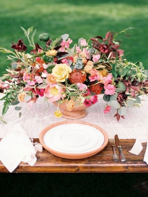 a bright spring wedding centerpiece in yellow, reds, pink, burgundy and with lots of greenery looks warm and cool