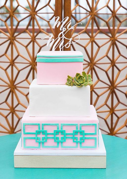 a bright square wedding cake with pink and green tiers with geometric patterns, a succulent and a chic topper