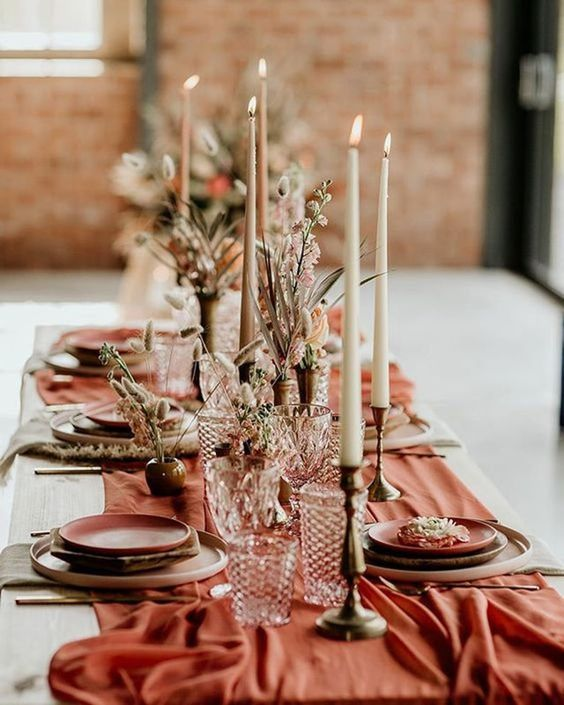 a bright terracotta wedding table runner and matching plates make the tablescape very bold and cool