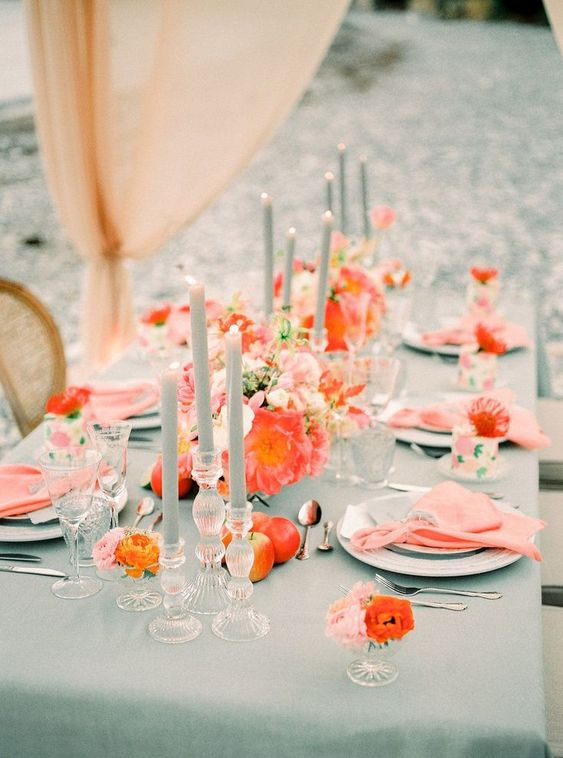 a bright wedding tablescape with a mint tablecloth, mint candles, coral napkins and blooms, orange flowers and apples looks wow