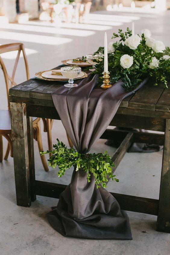 a charcoal grey wedding table runner accented with greenery is a refined and unusual wedding decor idea