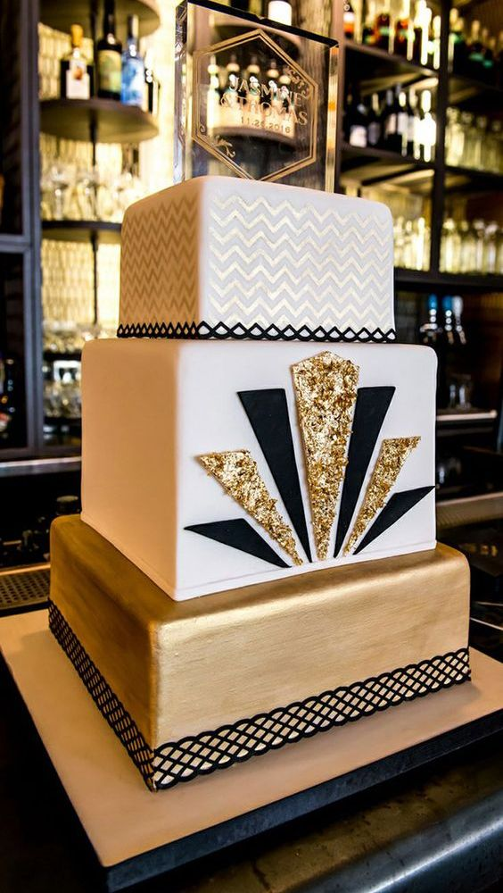 a chic art deco wedding cake with a chevron tier, a white tier with gold glitter and black and a gold tier
