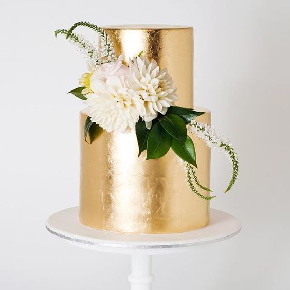 a chic gold leaf wedding cake with greenery and neutral blooms looks elegant and very bold