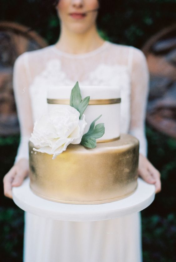 a classic elegant wedding cake with a white and gold tier, with a large white sugar bloom and leaves