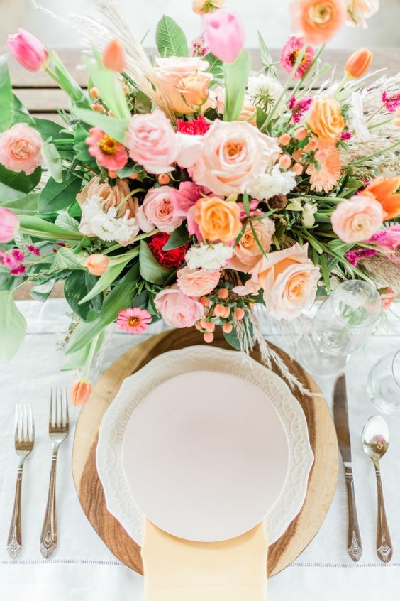 a colorful spring wedding centerpiece in light pink, blush, peachy and with much textural greenery
