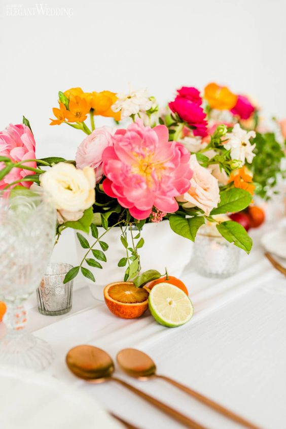 a colorful spring wedding centerpiece in pink, blush, white and marigold plus greenery