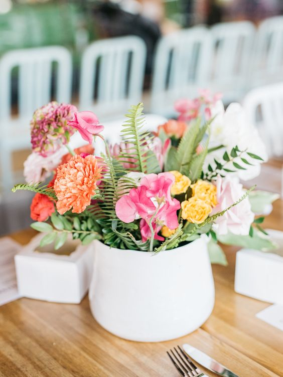 a colorful spring wedding centerpiece in pink, orange, yellow and with some greenery