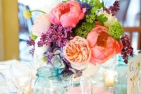 a colorful spring wedding centerpiece in pink, peachy, purple, greenery and with some texture for interest
