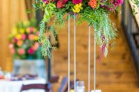 a colorful tall wedding centerpiece in fuchsia, light pink, yellow and some cascading greenery