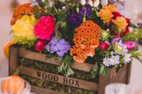 a colorful wedding centerpiece of a wooden box with moss, yellow, marigold, purple and hot pink blooms