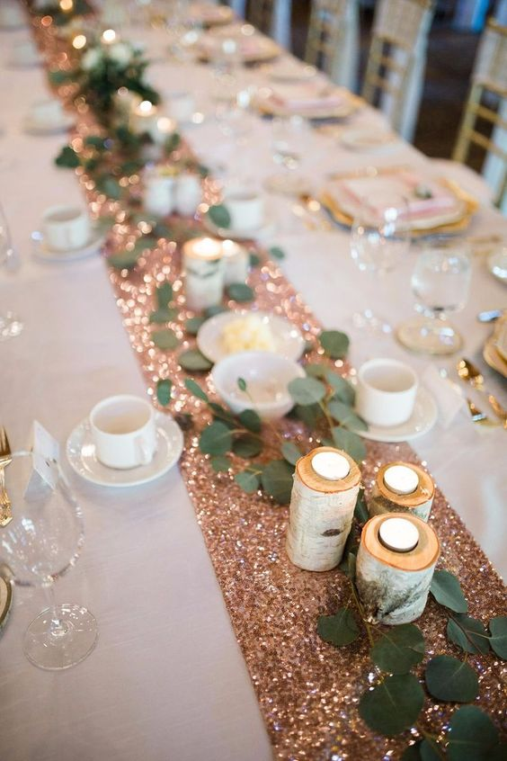 a copper sequin wedding table runner with tealights in logs and greenery is a very glam idea