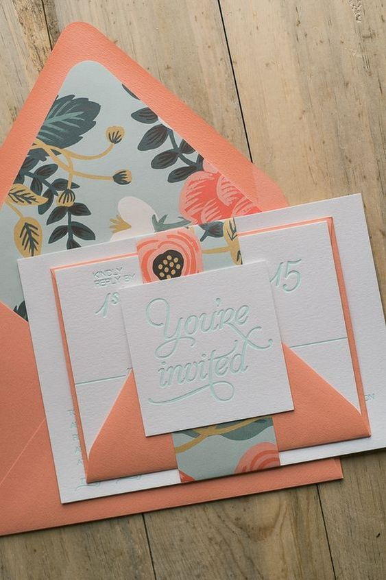 a coral, mint and white wedding invitation suite with floral lining and patterns plus cool geometry
