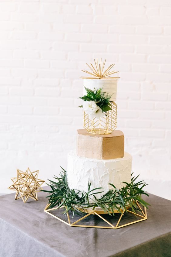 a creative modern wedding cake with textural white and a gold tier, greenery and white blooms