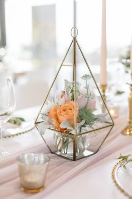 a creative terrarium with light mint greenery and coral blooms is a pretty and chic wedding centerpiece to rock