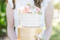a cute wedding cake with a gold and white and gold polka dot tier and lots of pink and white blooms