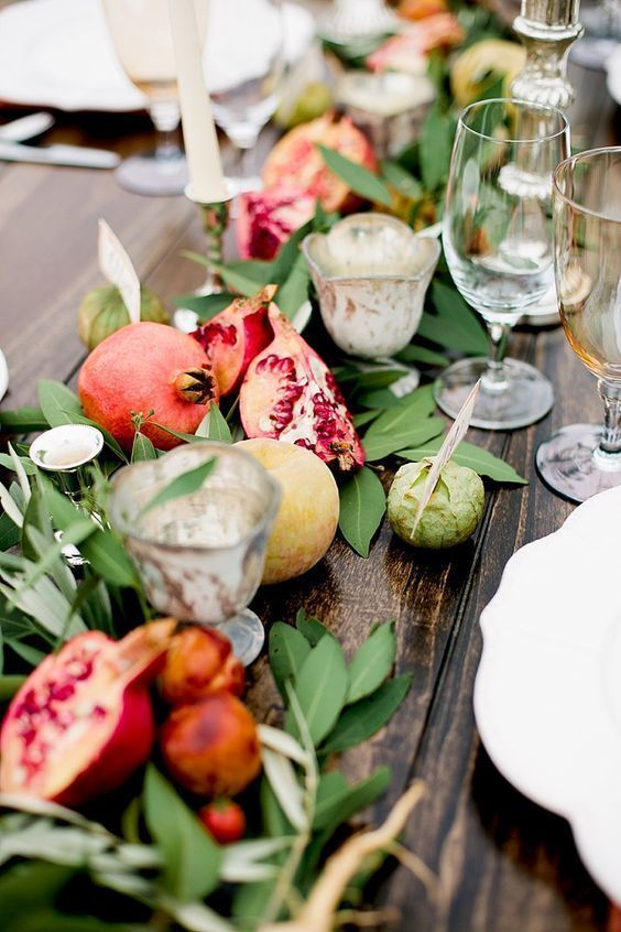 a fall wedding table runner of greenery, apples, pomegranates and candles is a very lush and cool idea