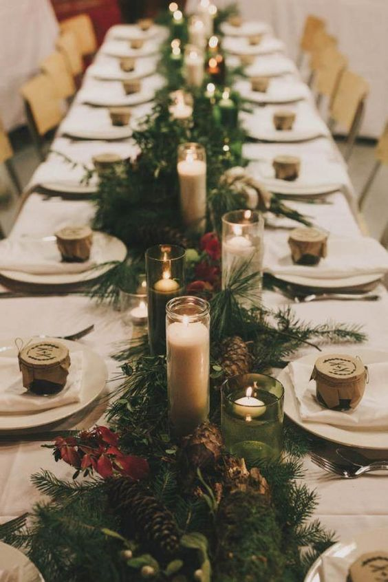 a fir table runner, pinecones, floating and usual candles for a wintery or Christmas wedding table