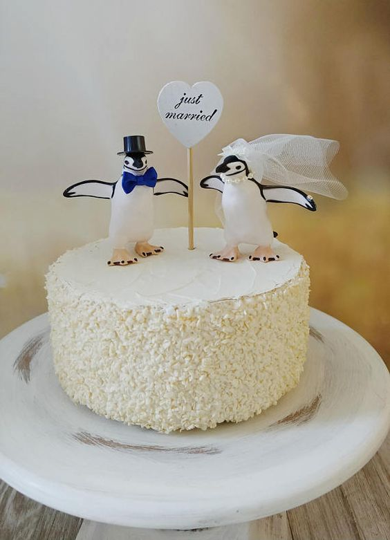 a fun white buttercream wedding cake with cheerful penguin toppers showing off the couple and a heart topper is amazing