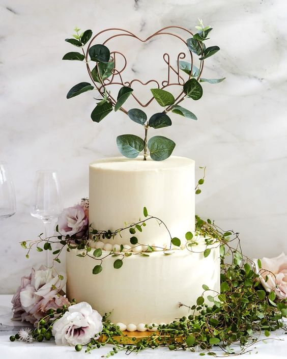 a garden wedding cake with greenery and blush blooms, a wire and leaf heart cake topper is a very beautiful and delicate idea to rock