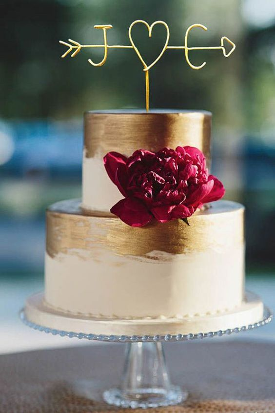 a glam white and gold brushstroke wedding cake with a burgundy bloom and a gold arrow cake topper with monograms and a heart is a cool idea