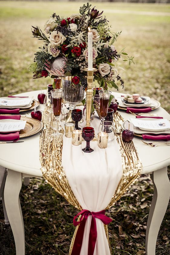 a gold sequin and white fabric table runners with a burgundy ribbon bow and burgundy napkins and glasses