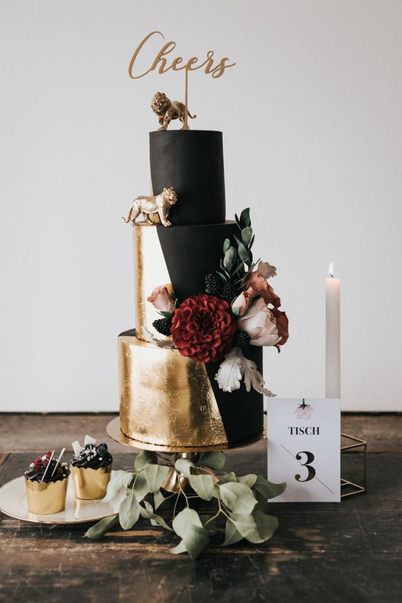 a gorgeous modern wedding cake in matte black and gold leaf, with fresh blooms, blackberries and gold figurines