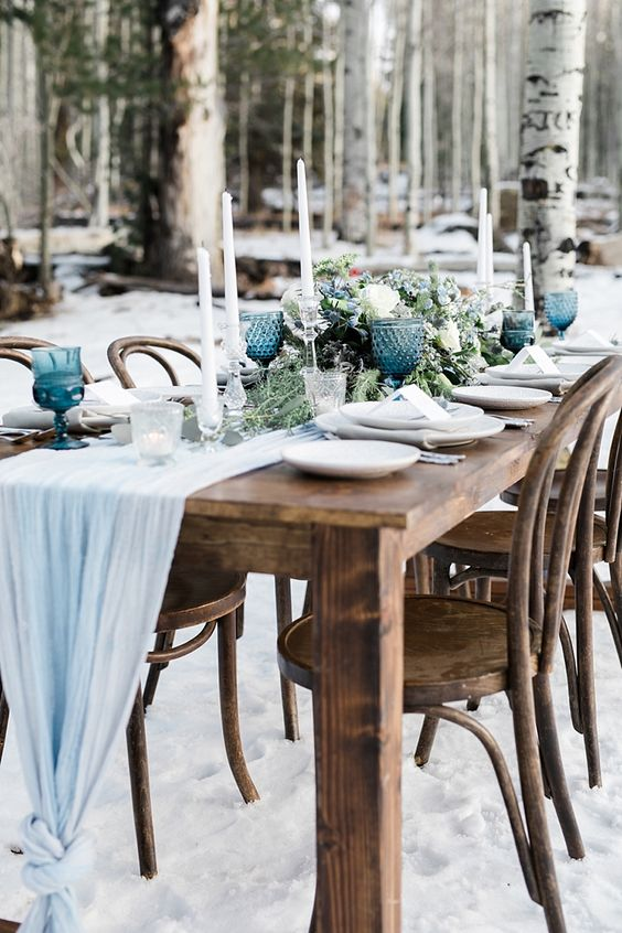 a light blue fabric table runner, blue glasses and blooms create a frozen feel at the winter wedding table