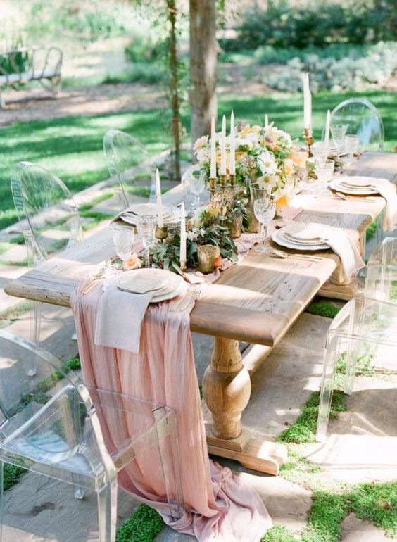a light pink fabric table runner paired with greenery and neutral napkins for a beautiful spring wedding table