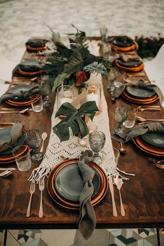 a macrame wedding table runner and centerpieces of tropical leaves for a boho tropical wedding