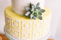 a mid-century inspired wedding cake with a white tier and a geometric yellow one plus a single succulent