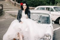 a midi A-line wedding dress with a full skirt, a black lather jacket, Hollywood waves and a red flower