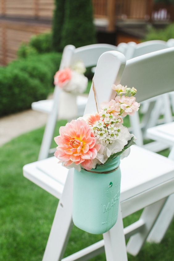 a mint jar with coral and white blooms and greenery to highlight the chairs of your wedding aisle