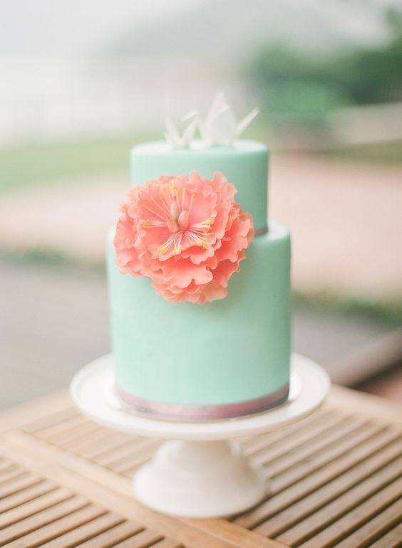 a mint wedding cake with a coral sugar bloom and edible origami is a cool idea for a bright wedding