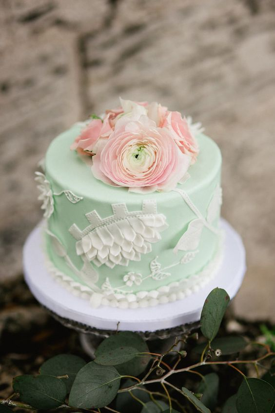 a mint wedding cake with white detailing and fresh coral blooms on top is a gorgeous idea for a wedding