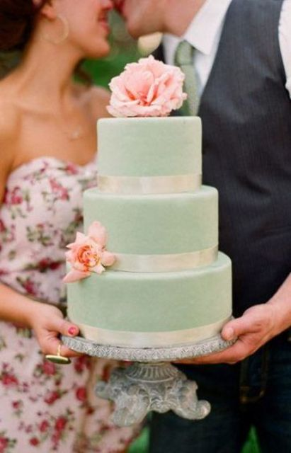 a mint wedding cake with white ribbons and coral blooms is a cool dessert for a wedding with a color scheme