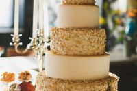 a modern refined wedding cake with white and gold confetti tiers is a chic and refined idea