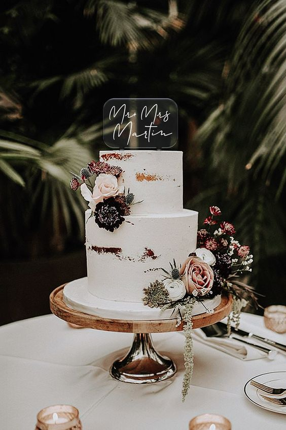a modern tropical wedding cake - a naked piece decorated with blush, pink, white an deep purple blooms and greenery plus an acrylic cake topper