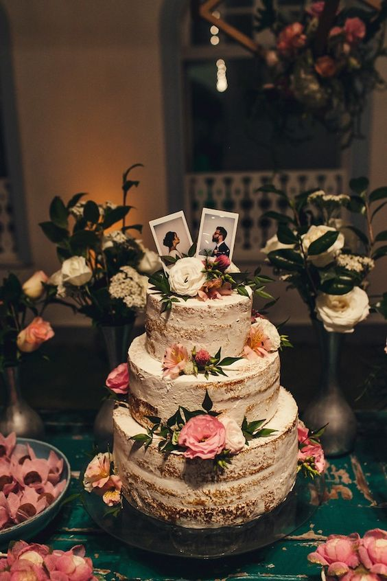 a naked wedding cake topped with pink, white and blush blooms, greenery and Polaroid photo cake toppers is very creative