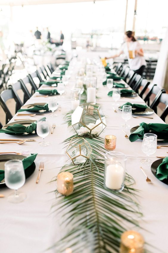 a palm leaf table runner with candles and votives and green napkins that match is a chic tropical idea