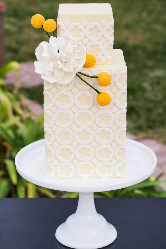 a pastel yellow and white patterned wedding cake decorated with a sugar flower and billy balls