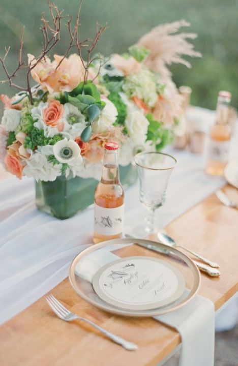 a pretty mint, coral and white wedding tablescape with a floral centerpiece, twigs and peach lemonade