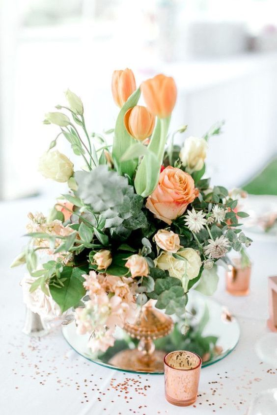 a pretty wedding centerpiece of coral and cremay blooms and lots of textural greenery for a texture