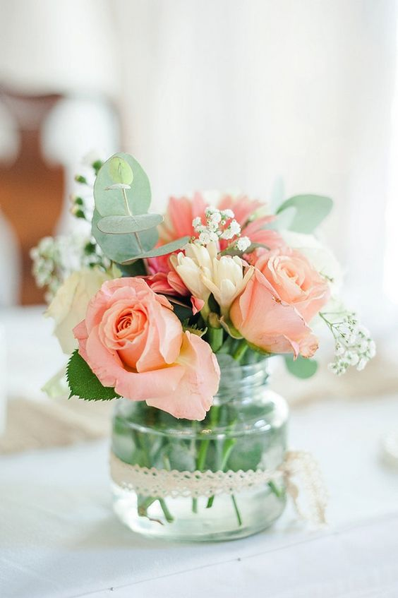 a pretty wedding centerpiece with eucalyptus, baby's breath, coral roses and lace ribbon on the jar