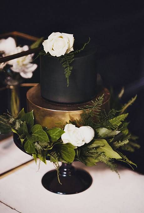 a refined and chic matte black and shiny gold wedding cake with lush greenery and white roses is elegant