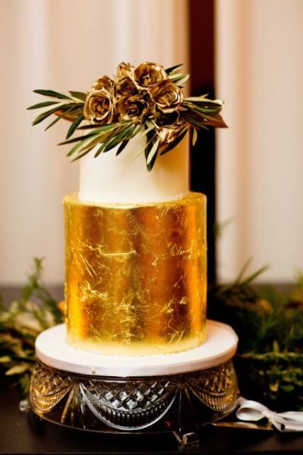 a refined fall wedding cake with a white and gold leaf tier with gilded blooms and greenery on top