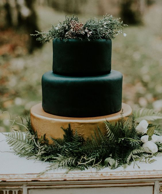 a refined modern wedding cake with matte black and a gold tier, with greenery and wildflowers on top