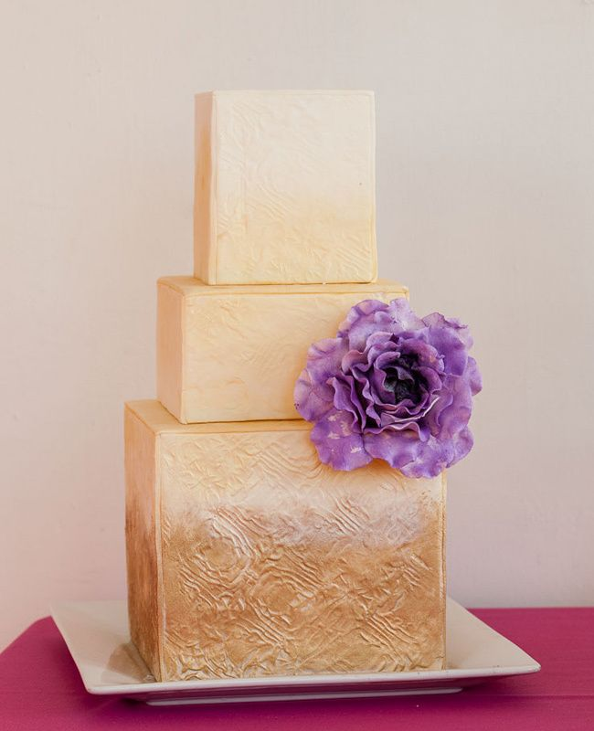 a refined patterned gold square wedding cake with a purple sugar bloom looks spectacular and wow
