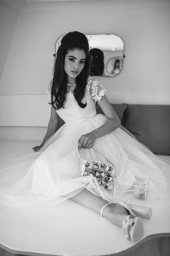 a retro-inspired bridal look with a perfect half up hairstyle, a midi wedding dress with a lace bodice and high heels