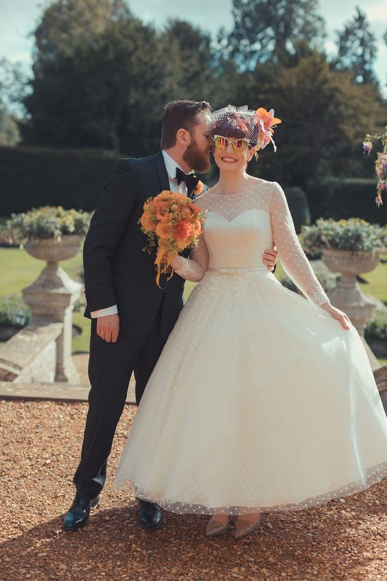 a retro inspired bridal look with a polka dot midi A line wedding dress, an illusion neckline and long sleeves